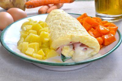 Rotolo di frittata farcito accompagnato da patate e carote